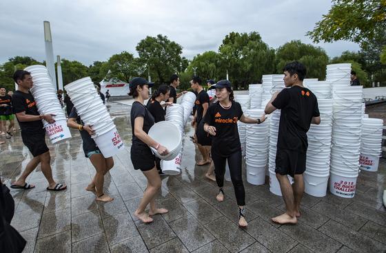 아이스버킷챌린지를 마친 참가자들이 버킷을 모아 한곳에 쌓고 있다. 박종근 기자