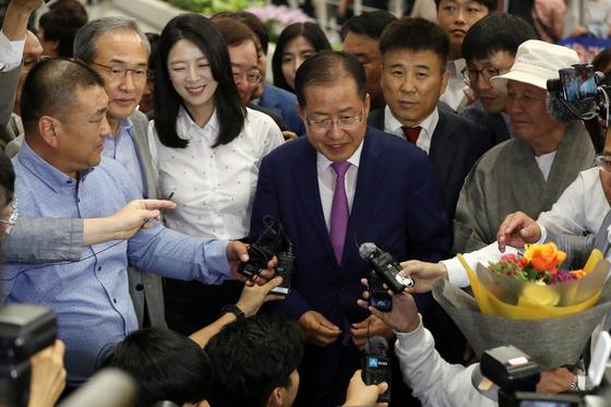 홍준표 전 자유한국당 대표가 15일 오후 인천국제공항을 통해 귀국해 쥐재진 질문에 답하고 있다. [뉴스1]
