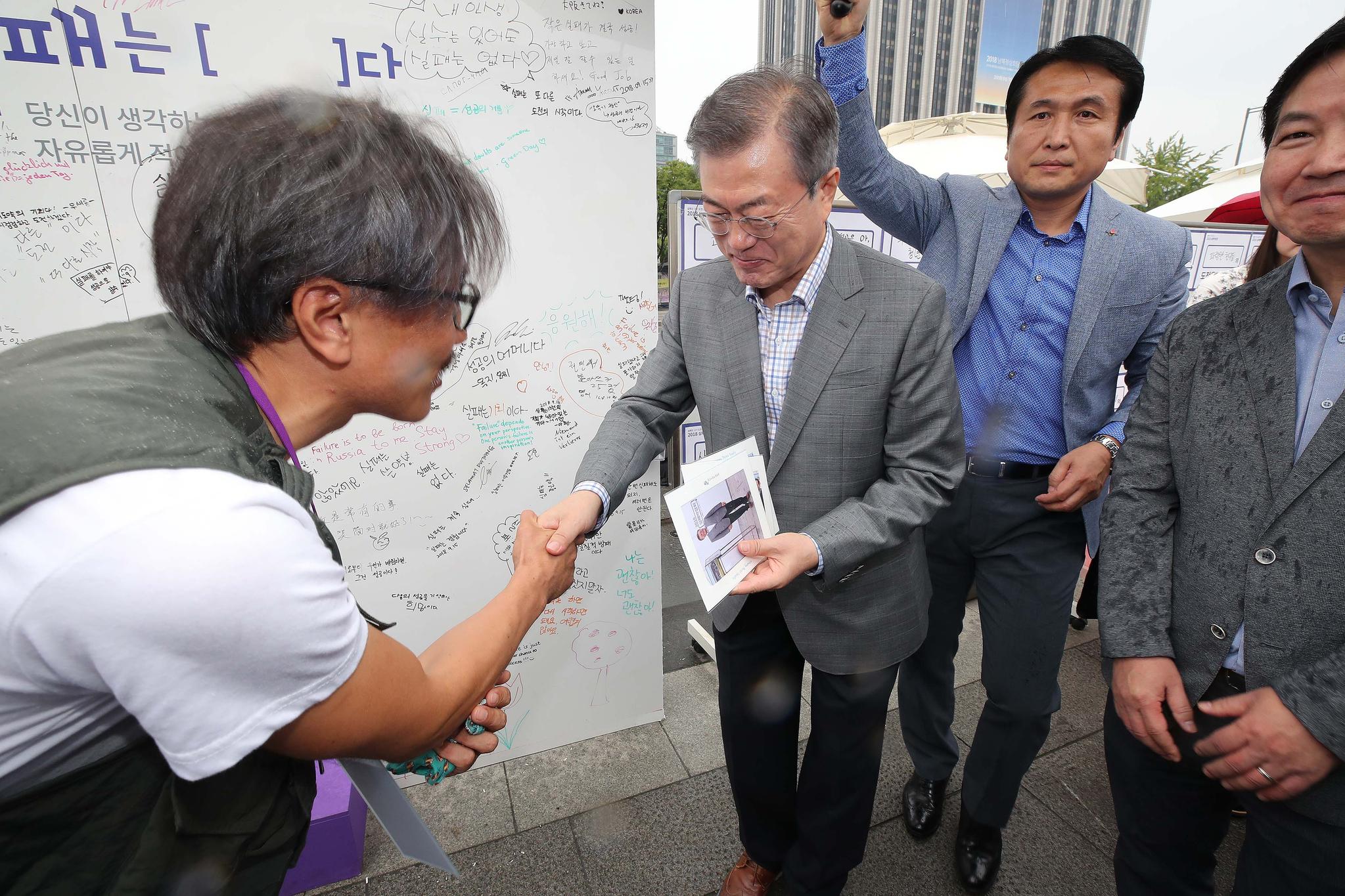 문재인 대통령이 16일 오후 서울 종로구 광화문 광장 일대에서 열린 2018 실패박람회를 방문해 노숙인에서 재기한 희망사진가에게 기념 촬영했던 사진을 선물 받고 있다. [뉴시스]