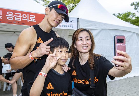 수원에서 12살 아들과 함께 행사에 참가한 김희경씨가 가수 션과 기념사진을 찍고 있다. 박종근 기자
