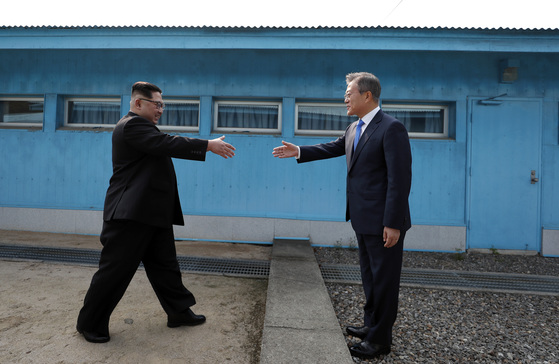 문재인 대통령과 북한 김정은 국무위원장이 4월 27일 판문점 군사분계선을 사이에 두고 인사하고 있다.공동취재단