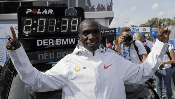 케냐의 엘리우드 킵초게가 세계기록을 세우며 골인한 뒤 2시간1분39초가 새겨진 전광판 앞에서 두손을 치켜들고 기뻐하고 있다. 킵초게는 이날 마라톤 사상 최초로 2시간 1분대를 기록했다. [베를린 AP=연합뉴스]