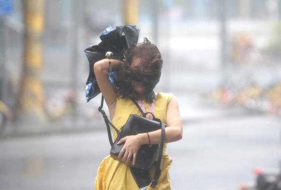 16일 태풍 망쿳의 영향으로 중국 광둥성 선전시 일대에 비가 세차게 내리는 가운데, 한 여성이 힘겨운 발걸음을 재촉하고 있다. [로이터=연합뉴스]