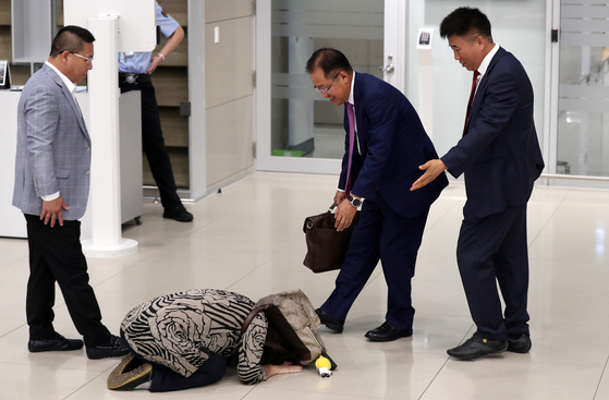 홍준표 전 자유한국당 대표가 15일 오후 인천국제공항을 통해 귀국해 한 지지자에게 큰절을 받고 있다. [뉴스1]