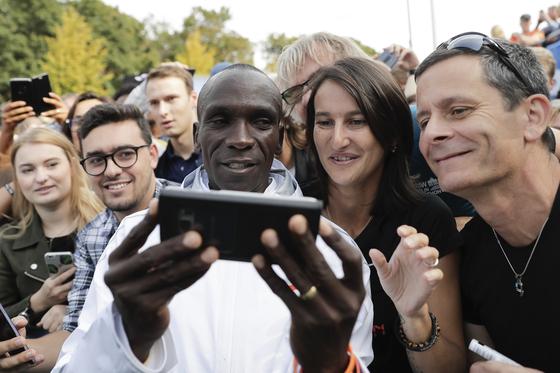 16일 열린 2018 베를린 국제 마라톤에서 팬들과 함께 셀카를 찍는 케냐의 엘리우드 킵초게(가운데). [AP=연합뉴스]