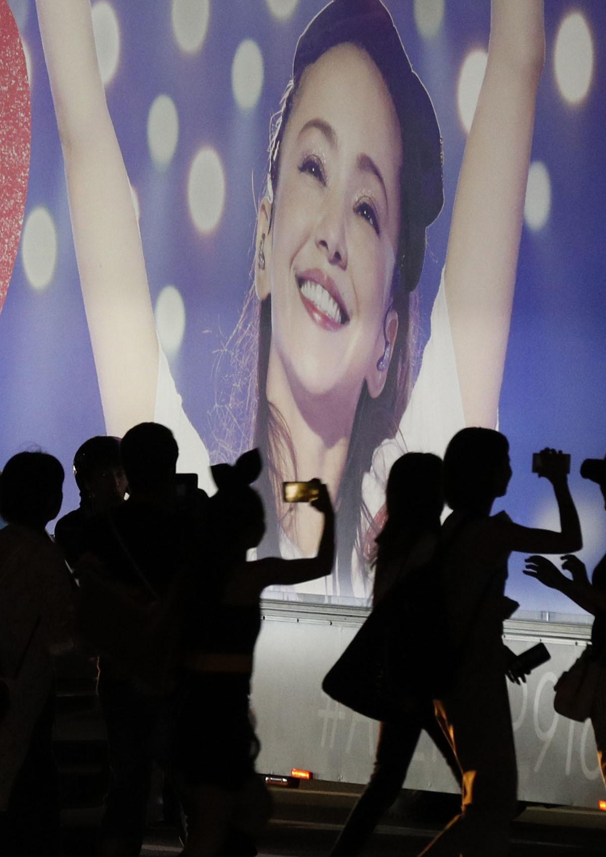 15일 저녁 오키나와(沖繩)현 기노완(宜野彎)시에서 열린 아무로 나미에의 은퇴 기념 콘서트장에 설치된 가수의 사진 앞에서 팬들이 모여 있다. [연합뉴스]