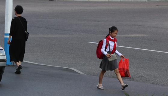 수업을 마친 한 여학생이 평양 고려호텔 앞을 걸어가고 있다.평양사진공동취재단