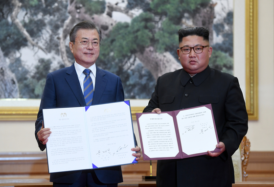 문재인 대통령(왼쪽)과 김정은 북한 국무위원장이 19일 오전 평양 백화원 영빈관에서 평양공동선언문에 서명한 후 합의서를 들어보이고 있다. [평양 사진공동취재단]