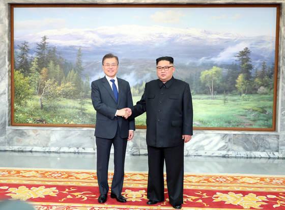 문재인 대통령(왼쪽)과 김정은 북 국무위원장이 지난 4월 판문점 정상회담에서 만났을 당시 백두산 그림 앞에서 기념촬영을 하고 있다. [청와대 제공]