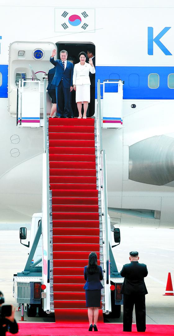 """문재인 대통령과 부인 김정숙 여사가 18일 오전 평양 순안공항에 도착해 전용기 트랩 아래까지 마중 나온 김정은 북한 국무위원장 내외와 인사하고 있다. 청와대는 '김 위원장 내외의 공항 영접은 이번이 처음""""이라며 '외국 정상회담에서도 찾아보기 어려운 환대""""라고 밝혔다. [평양사진공동취재단]"""