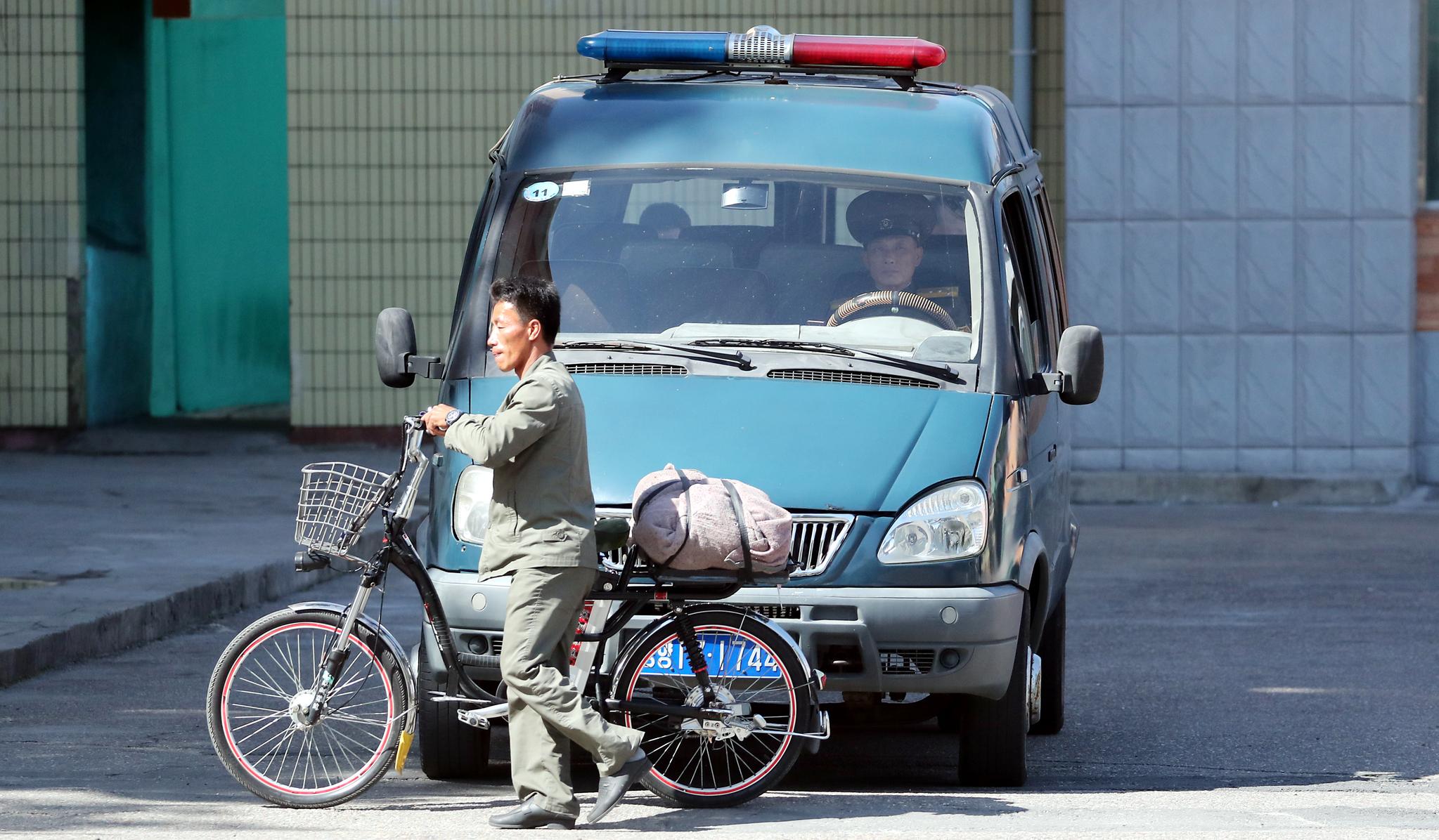 한 북한 군인이 차 앞으로 자전거가 지나가자 멈춰서 기다리고 있다.평양사진공동취재단