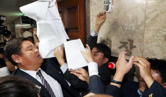 참여연대, 경실련, 금융정의연대 등 시민단체 회원들이 17일 서울 여의도 국회에서 열린 더불어민주당 의원총회장앞에서 은산분리 완화 시도를 중단 촉구를 하다 제지하는 국회 경위들과 몸싸움을 하고 있다. [뉴스1]