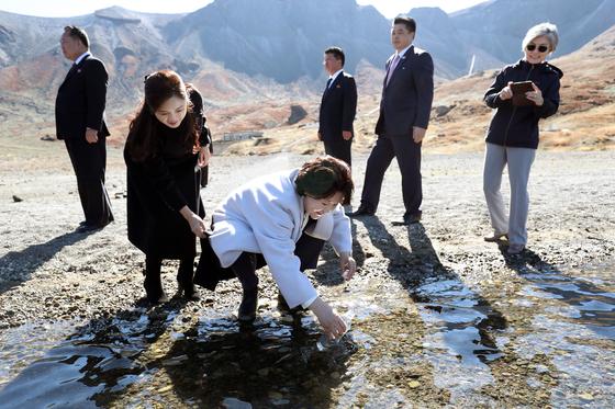 문재인 대통령 부인 김정숙 여사가 20일 오전 김정은 국무위원장 내외와 백두산 천지를 산책하던 중 천지 물을 물병에 담고 있다.