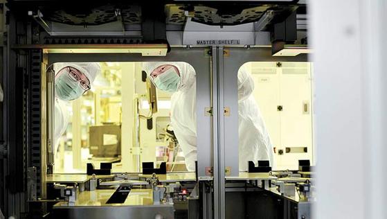 SK하이닉스는 기술 혁신을 통해 글로벌 반도체 시장을 선도해 나가고 있다. 사진은 SK하이닉스 임직원이 반도체 생산 장비의 내부를 들여다 보고 있는 모습. [사진 SK하이닉스]