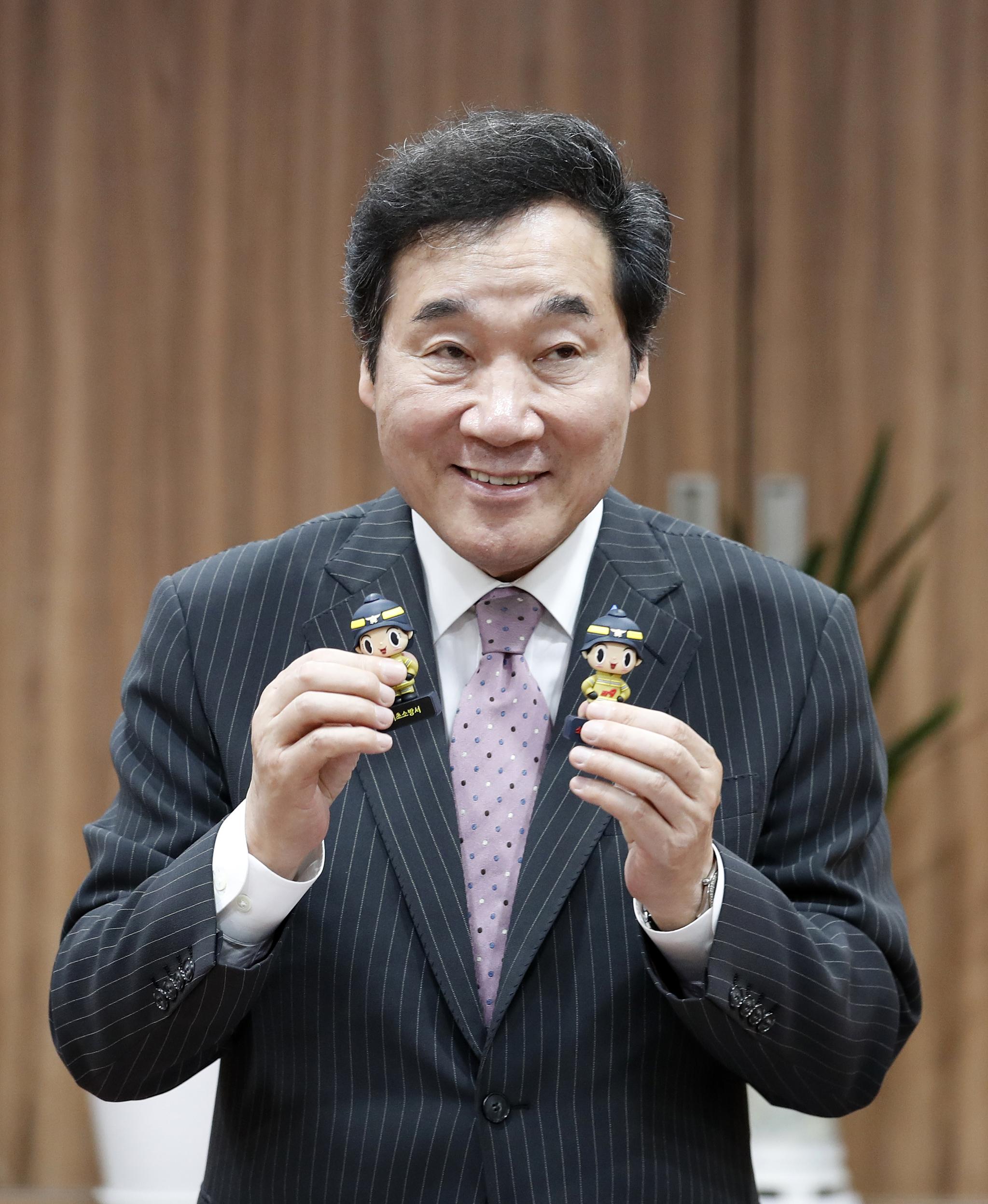 이낙연 국무총리가 20일 오후 서울 서초구 서초소방서를 방문해 소방관 기념품을 들고 있다. [뉴스1]