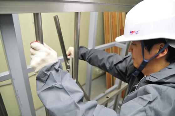 한국건설생활환경시험연구원(KCL) 안전융합기술센터 연구원이 시중에 판매되는 알루미늄 방범용 창살의 강도를 확인해보고 있다. 발로 찬 충격에 휘어진 창살을 손으로 분리하고 있다 [사진제공=KCL]
