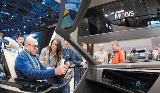 지난 1월 열린 2018 CES에서 현대모비스 부스를 찾은 관람객이 설명을 들으며 전시품을 체험해보고 있다. 현대모비스는 7년 연속 글로벌 부품업체 순위 10위 안에 올랐다. [사진 현대모비스]