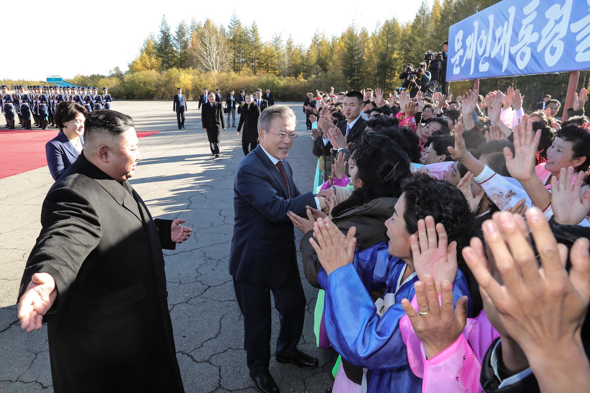 문재인 대통령이 20일 오전 백두산 등정을 위해 삼지연 공항에 도착한 뒤 환영 나온 주민들과 인사하고 있다.왼쪽 김정은 위원장이 문 대통령을 안내하고 있다. 평양사진공동취재단