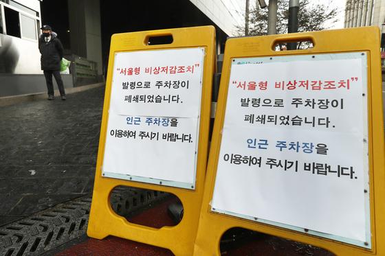 지난 1월 초미세먼지로 인해 미세먼지 저감조치가 시행됐다. 출·퇴근시 서울 지하철과 버스는 무료로 운영되며 공공기관 주차장 폐쇄와 차량 2부제가 시행되었다. 이날 폐쇄된 서울시청 주차장 입구에서 안내요원이 주차안내를 하고 있다. [중앙포토]