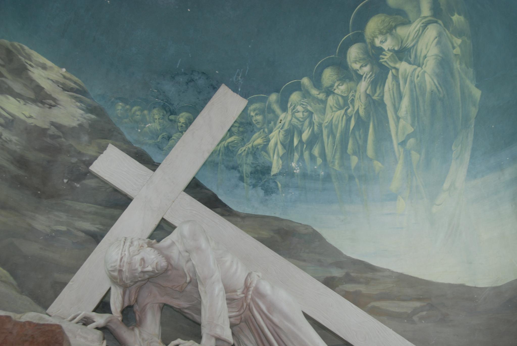 십자가를 짊어진 채 걸어가다가 쓰러지는 예수. 십자가의 길에 있는 교회 벽면에 그려져 있다.