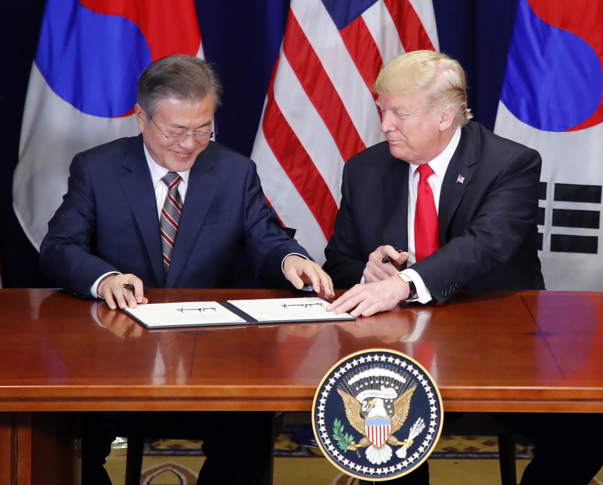 문재인 대통령과 트럼프 대통령이 24일 미국 뉴욕 롯데 뉴욕팰리스 호텔에서 열린 '한미 자유무역협정(FTA) 서명식'에서 '한미 자유무역협정(FTA)에 관한 공동성명'에 서명하고 있다. [연합뉴스]