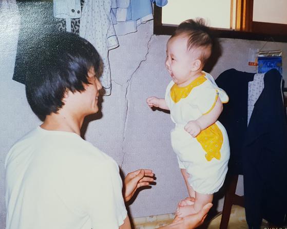 """아빠는 무뚝뚝한 성격으로 나를 """"우리 딸""""이라고 불러본 적도 없다. 20대까지는 그런 아빠한테 많이 섭섭하기도 했지만 최근에는 아빠 나름의 방식으로 사랑을 주는 게 느껴진다. 지금은 고민이 있을 때마다 든든한 상담자 역할을 해주신다. 사진은 내가 6개월 때 아빠가 놀아주는 모습. 아빠는 지금도 돌이 안 된 작은 아기를 보면 한손에 올려 놀아주신다. [사진 서영지]"""