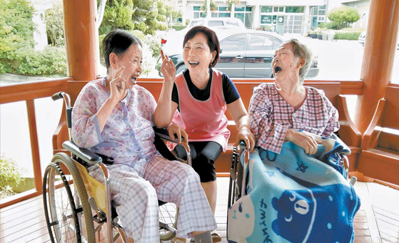 노인장기요양보험이 시행 10년만에 노인성 질환자와 가족의 부담을 크게 줄였다. 사진은 요양시설에서 환자가 요양보호사(가운데)와 즐거운 시간을 보내는 장면이다. 사진 공모전 수상작이다. [사진 건강보험공단]
