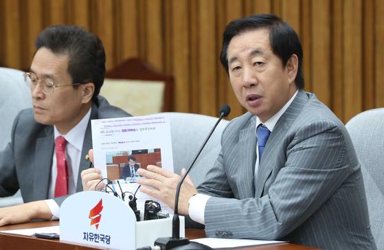 자유한국당 김성태 원내대표(오른쪽)가 28일 국회에서 열린 원내대책회의에서 업무추진비 사적 사용으로 해임당한 강규형 전 KBS 이사의 보도자료를 들어 보이고 있다. 오종택 기자