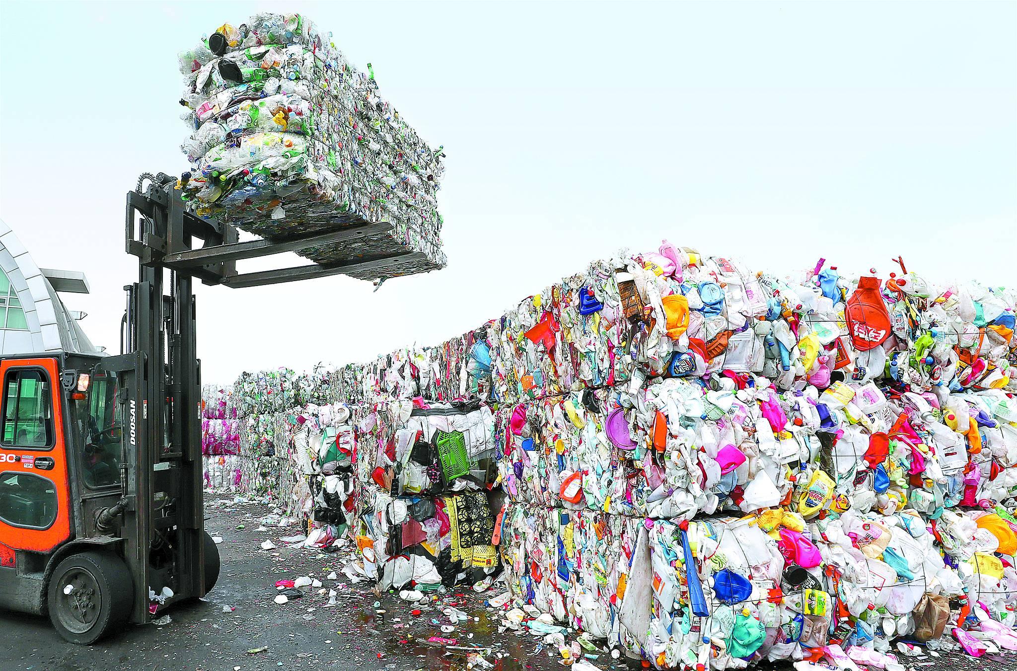 지난 4월 수도권 지역에서는 재활용업체가 폐비닐 수거를 거부하는 사태가 빚어져 시민들이 불편을 겪었다. 사진은 경기도 용인시 재활용센터에서 직원이 압축 플라스틱을 정리하는 모습. [뉴스1]