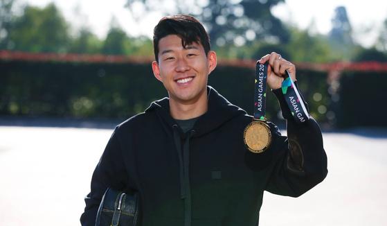 손흥민이 아시안게임 금메달을 꺼내보이고 있다. [사진 토트넘홋스퍼 구단 홈페이지]