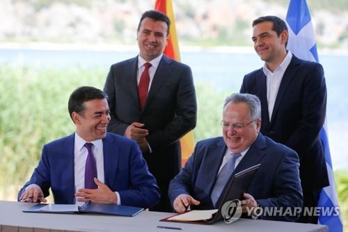 지난 6월 국호 변경 합의안에 서명하는 그리스와 마케도니아 외무장관. 뒤에서 두 나라 총리가 지켜보고 있다.[로이터=연합뉴스]