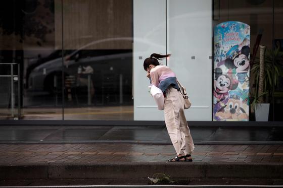 24호 태풍이 강타한 가고시마에서 한 여성이 돌풍을 뚫고 걷고 있다. [AFP=연합뉴스]