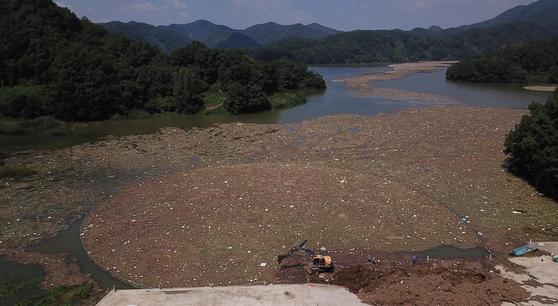 대청호 부유물 처리장 주변에 떠있는 쓰레기. 멀리 부유물 차단막에도 쓰레기가 걸려 있다. [연합뉴스]