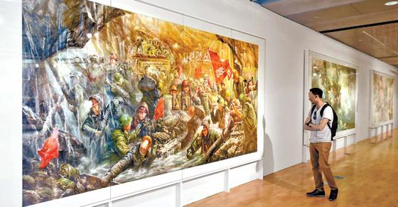 '2018 광주비엔날레'를 찾은 관람객이 북한의 미술작품을 관람하고 있다. 올해 비엔날레는 '상상된 경계들'을 주제로 11월 11일까지 열린다. [뉴시스]