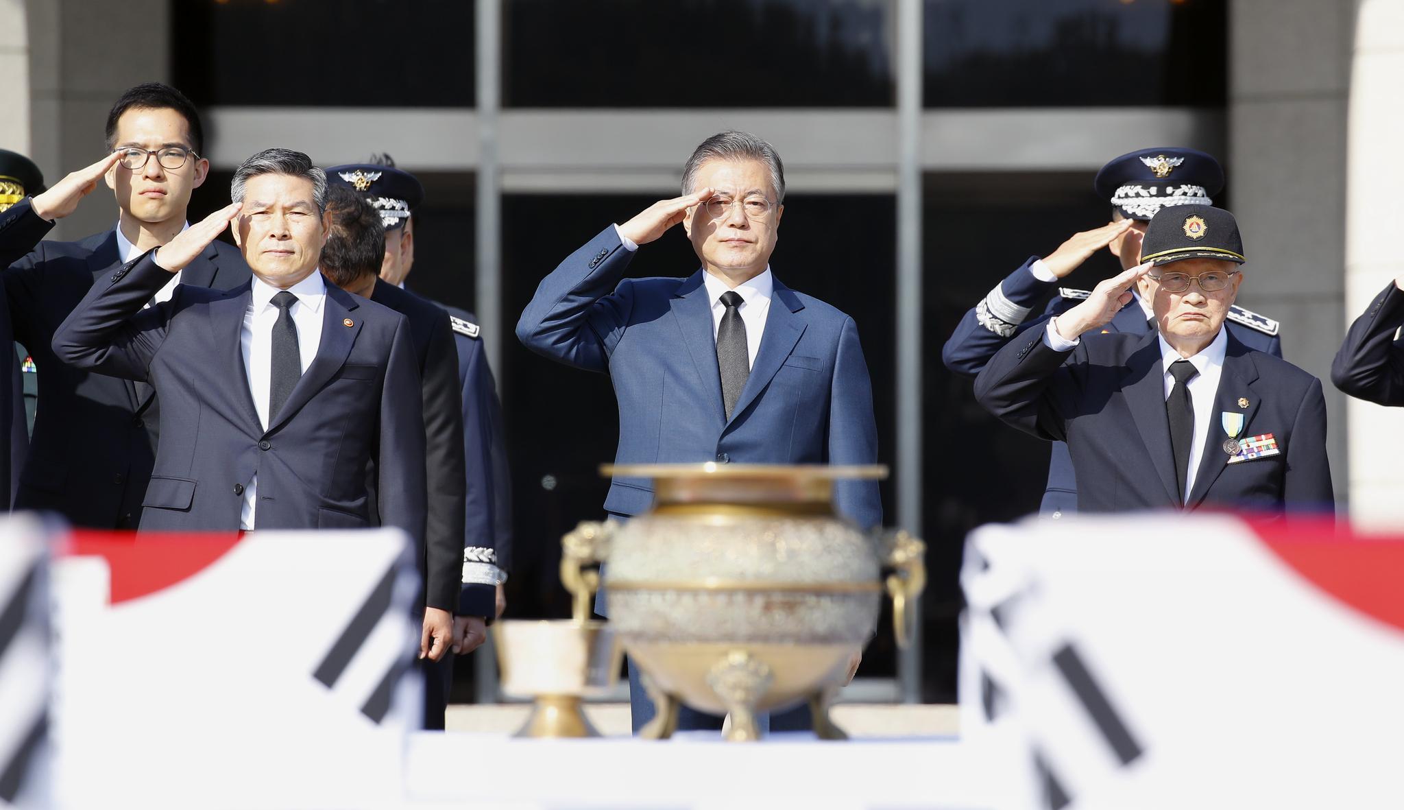 문재인 대통령이 국군의 날인 1일 오전 서울공항에서 열린 국군 유해 봉환행사에서 64위의 6.25 참전 국군 전사자에 대해 경례를 하고 있다. [연합뉴스]