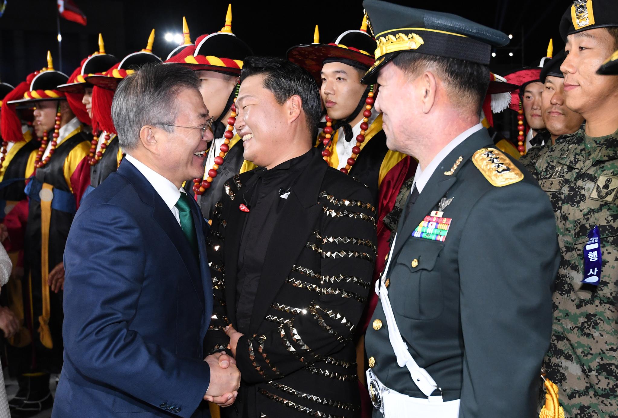1일 오후 서울 용산 전쟁기념관 평화의 광장에서 열린 제70주년 국군의 날 기념식에서 문재인 대통령(왼쪽)이 가수 싸이와 악수하고 있다. [청와대사진기자단]