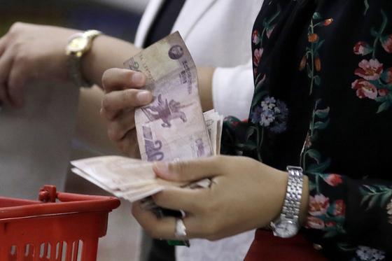 지난달 12일 북한 주민이 평양의 마트에서 장을 본 뒤 계산대에서 현금을 세고 있다. [AP=연합뉴스]