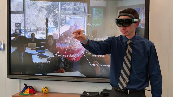 지난달 14일 호주 캔버라 그래머스쿨에서 이 학교 매튜 퍼셀 교사가 혼합현실(MR) 기기 '홀로렌즈'를 얼굴에 쓰고 심장에 관해 설명하고 있다.. 교사의 눈에 비친 광경이 실시간으로 교실 뒤 스크린에 투영되고 있다. 이 학교는 3차원 실체에 대한 이해가 필요한 수업에 이 기기를 활용한다. [사진 강대석]