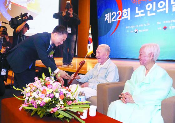 박능후 보건복지부 장관(왼쪽)이 2일 서울 중구 대한상공회의소 국제회의장에서 열린 '제22회 노인의 날 기념식'에서 100세 유칠상(가운데) 할아버지, 박순자 할머니께 장수지팡이 청려장을 전달하고 있다. [뉴스1]