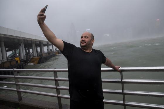 슈퍼태풍 망쿳이 휘몰아친 홍콩 선착장 앞에서 셀카 찍는 남성의 모습 [EPA=연합뉴스]