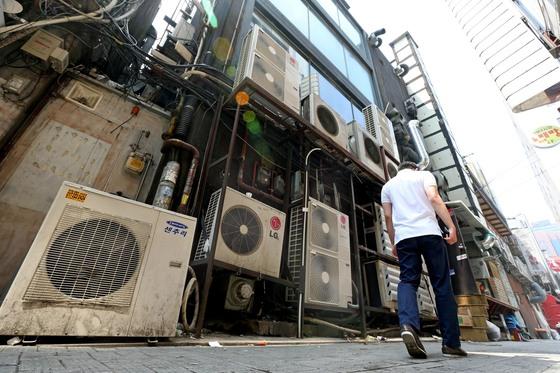 서울 종로구의 한 상점가에 에어컨 실외기가 빼곡하게 설치돼 있다. 규정상 2m 이상 높이에 설치돼야 하지만 많은 실외기가 바닥 등에 불법 설치돼 보행자를 향해 40도가 넘는 뜨거운 바람을 내뿜고 있었다. [중앙포토]
