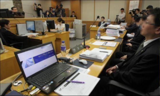 민사전자소송이 전면 시행된 이후 서울 신정동 남부지방법원에서 최초로 전자소송이 열렸다. 증거자료를 스크린에 보여주는 실물화상기가 변호인 석에 설치되어 있다.[중앙포토]
