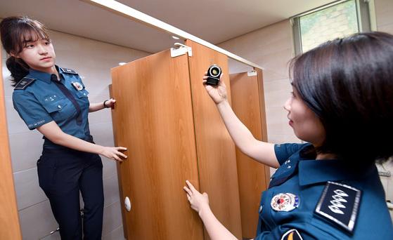 경찰이 여자 화장실에서 탐지기를 이용해 불법 촬영 기기를 찾고 있는 모습[뉴스1]