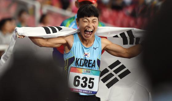 8일 육상 여자 200m T36 결승에서 전민재 선수가 1위로 결승선을 통과한 후 태극기를 들고 환호하고 있다. [사진공동취재단]