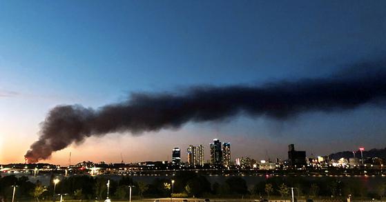 7일 저녁 경기도 고양시 저유소 화재로 발생한 검은 연기가 서울 도심으로 번져나가고 있다. [연합뉴스]