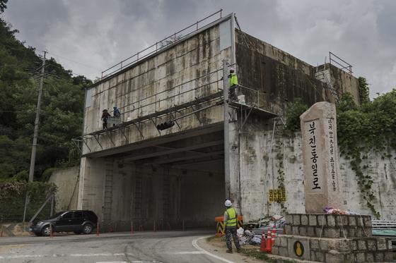 지난 8월 경기도 포천시 영중면 국도 43호선 대전차 방호시설에서 근로자들이 철거를 위해 사전 안전 작업을 벌이고 있다. 이 구간은 굽은 도로인데다가 구조물이 오래돼 교통사고의 위험이 컸으며 주민들은 10년 전부터 방호벽 철거를 요구했다. [연합뉴스]