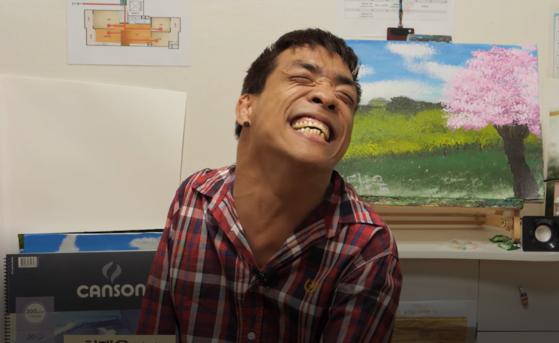 지난달 19일 경인장애인자립생활센터 체험홈에서 만난 입으로 그림을 그리는 구족화가 최태웅(38)씨. 그의 뒤에 보이는 그림은 가장 최근 그가 완성한 '어느 봄날'이라는 제목의 그림이다.