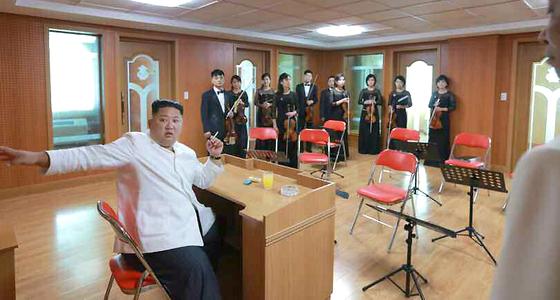 김정은 위원장이 왼손에 담배를 들고 연습실에서 단원들과 이야기하고 있다.책상 위에 재떨이도 보인다.[연합뉴스]