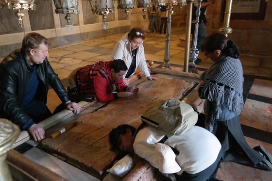 십자가에서 죽은 예수의 주검을 눕혔다고 전해지는 석판. 성묘교회 내부에 있는 이 석판에 얼굴을 댄 채 순례객들이 기도를 하고 있다.