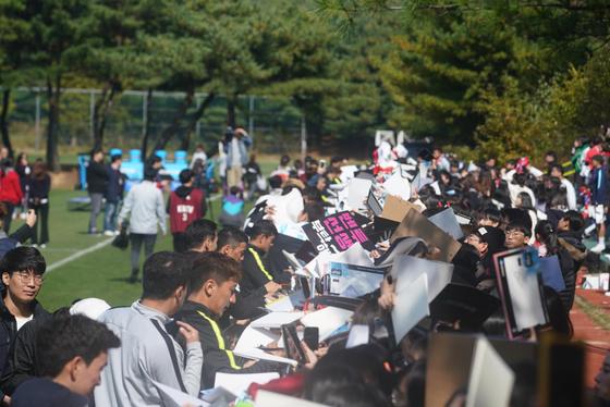 축구 대표팀 선수들이 파주 NFC에서 진행된 공개훈련 행사에 참가한 팬들에게 사인해주고 있다. [연합뉴스]